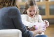 Caucasian mother giving gift to excited daughter