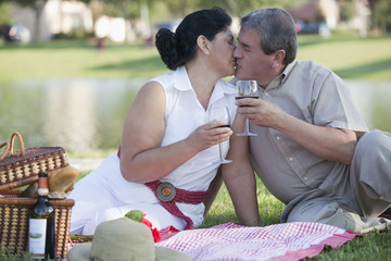 Hispanic couple kissing and drinking wine in park