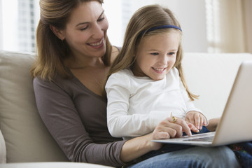 Caucasian mother and daughter using laptop together