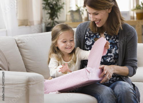 Caucasian mother watching daughter opening gift