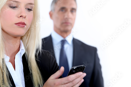 Woman with mobile and man in the background