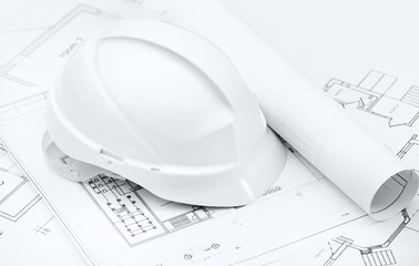 White hard hat on working or engineering drawings