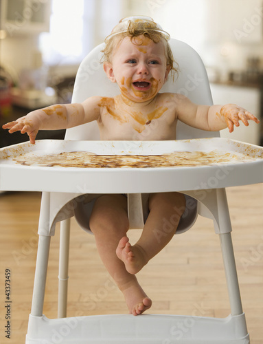 Crying, messy Caucasian baby boy sitting in high chair