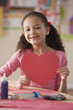 Hispanic girl holding Valentine's heart in classroom