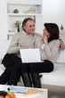 Mature couple relaxing in front of laptop