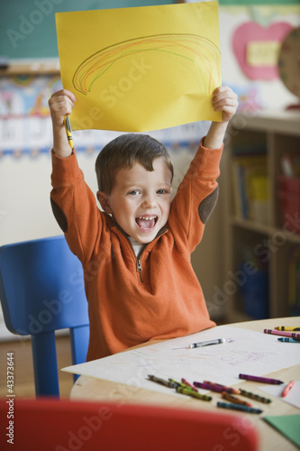 Caucasian boy holding up picture of rainbow