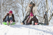 Father and daughters sledding on snow covered hill