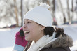 Hispanic girl talking on cell phone in snow