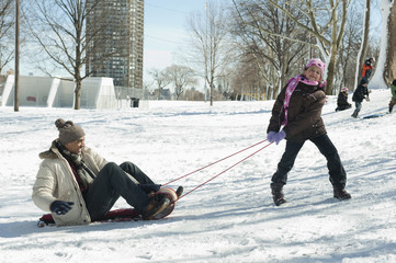 Daughter pulling father on sled
