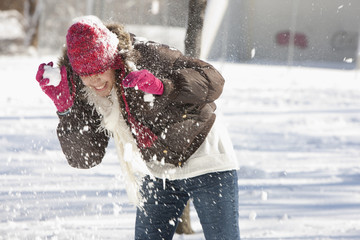Hispanic girl having snowball fight