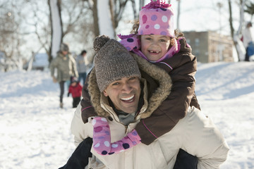 Father carrying daughter on back through snow