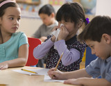 Mixed race girl blowing nose in classroom