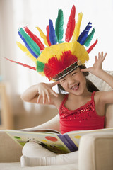 Mixed race girl reading book dressed in Indian costume making a face