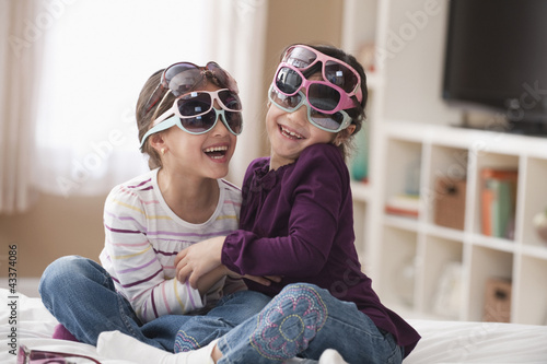 Playful girls trying on sunglasses