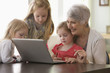 Caucasian grandmother and granddaughters using laptop together