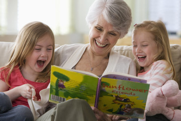 Caucasian grandmother reading book to granddaughters