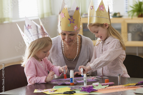 Caucasian grandmother and granddaughters doing arts and crafts together