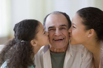 Hispanic girls kissing grandfather