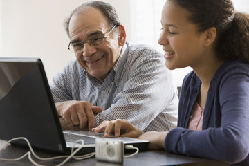 Hispanic girl and grandfather using laptop together