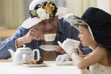 Hispanic girl and grandfather having tea party