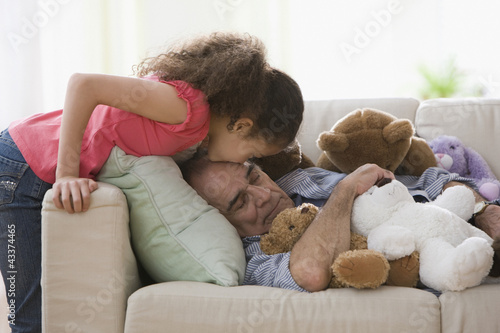 Hispanic girl kissing napping grandfather