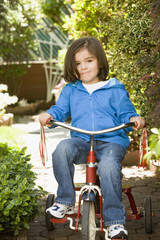 Mixed race boy riding tricycle