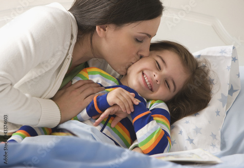 Mother kissing son in bed