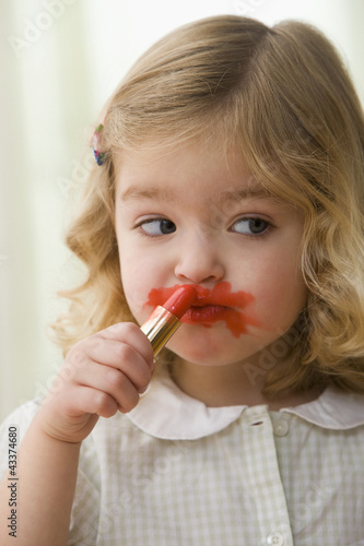 Caucasian girl putting on lipstick