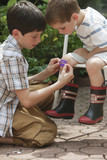 Boy putting bandage on brother's knee