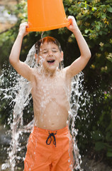 Caucasian boy pouring water over himself