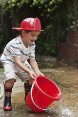 Caucasian boy playing with bucket wearing fireman's hat