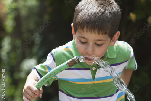 Caucasian boy drinking water from hose