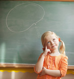 Caucasian girl standing near thought bubble on blackboard