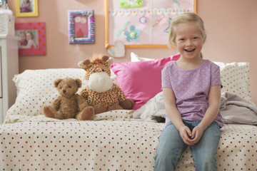 Smiling Caucasian girl sitting on bed