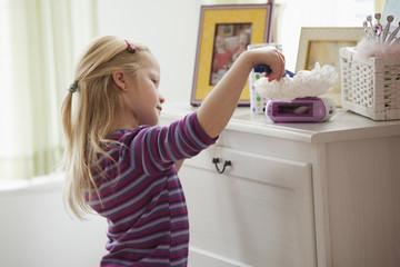 Caucasian girl dusting dresser