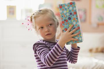 Caucasian girl holding birthday gift
