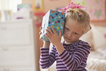 Caucasian girl listening to wrapped birthday gift