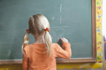 Caucasian girl solving math problem on blackboard