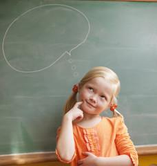 Caucasian girl standing near thought bubble on blackboard