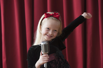 Caucasian girl singing into old-fashioned microphone