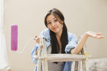 Caucasian woman holding paint roller