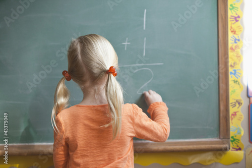 Caucasian girl solving math problem on blackboard