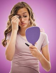 Caucasian teenager putting on mascara
