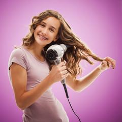 Caucasian teenager blow drying her hair