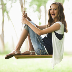Caucasian girl sitting on swing