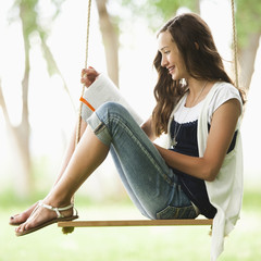 Caucasian girl reading book on swing