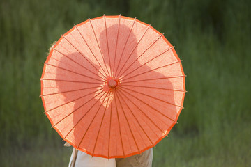 Caucasian couple standing behind parasol