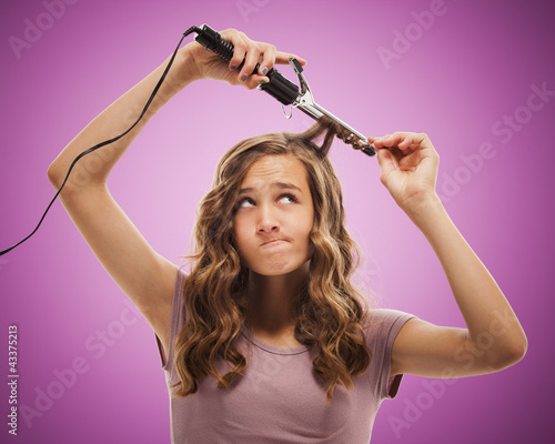 Caucasian teenager curling her hair