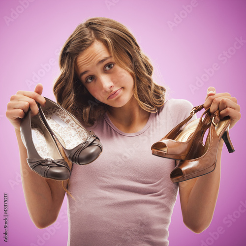 Uncertain Caucasian teenager holding shoes