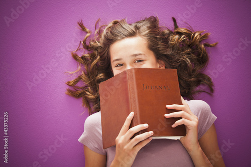 Caucasian teenager holding journal